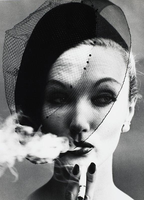 portrait of a woman with upswept hair, wearing a dark hat with a veil and holding a cigarette in front of her chin; woman exhales a cloud of smoke