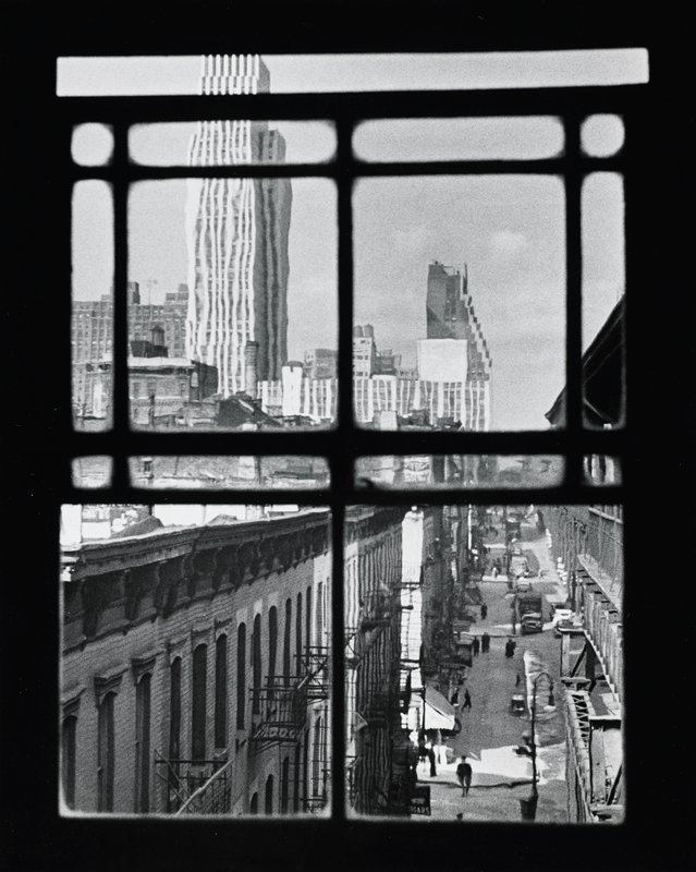 view of skyscrapers and city street with figures and cars, through a window with 15 panes