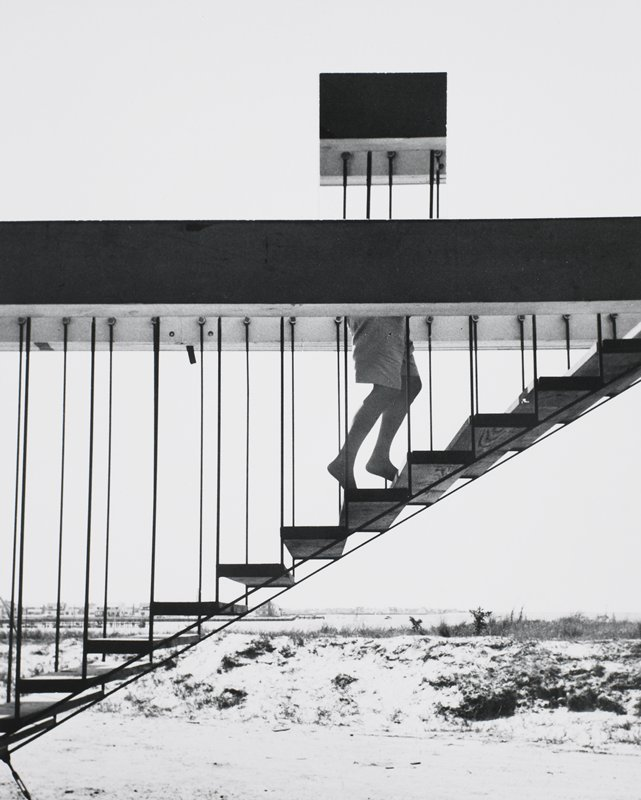 open, suspended staircase ascending up from a beach; legs and shorts of a figure ascending stairs - upper body hidden by beam