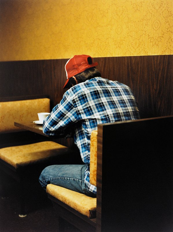 man wearing jeans, blue plaid shirt, and red and white cap, seen from back, sitting at a small restaurant booth with yellow upholstery