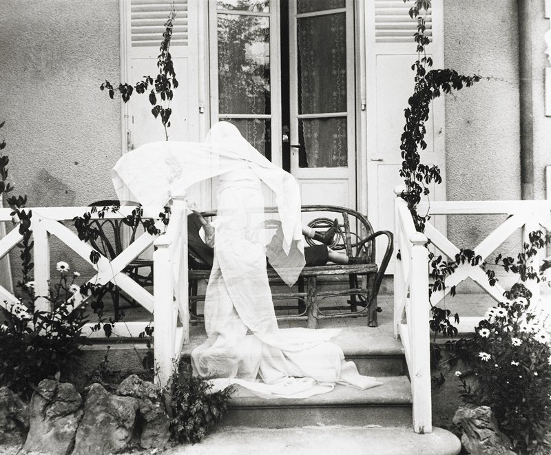 figure reclining on bench on a porch in front of open French door; ghostly figure appears transparent in front of reclining figure