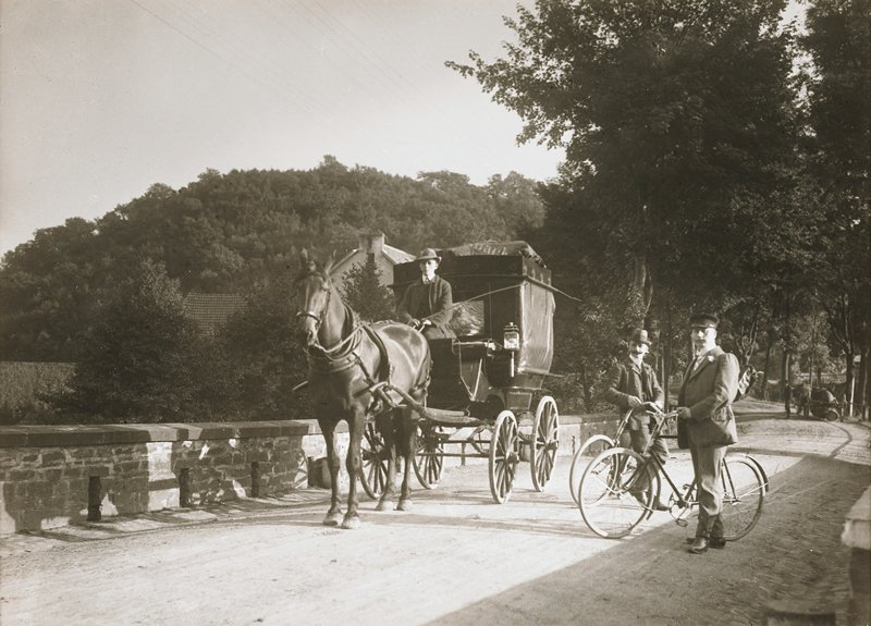 two men with bicycles at right; man seated on a closed horse-drawn carriage at left