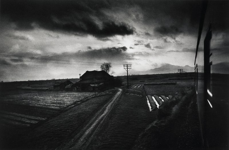 landscape farm fields with house in center middle, side of train at right edge; sky cloudy and dark