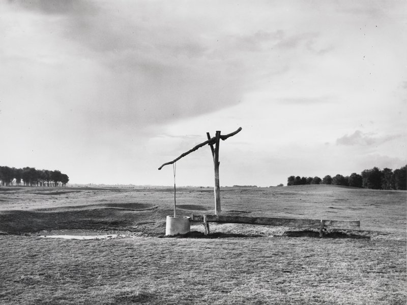 a well in the middle of open fields; distant trees left and right center ground
