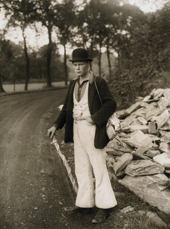 young man standing at the side of a road holding a spiral-carved walking stick; wearing hat, dark coat, white vest and pants, knit shirt with button front; bag over shoulder