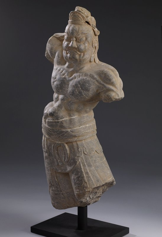armless figure--bottom edge at middle of thighs; heavily muscled torso; wearing skirt with tie at waist; frowning, angry expression; headdress; dark stone with white veins
