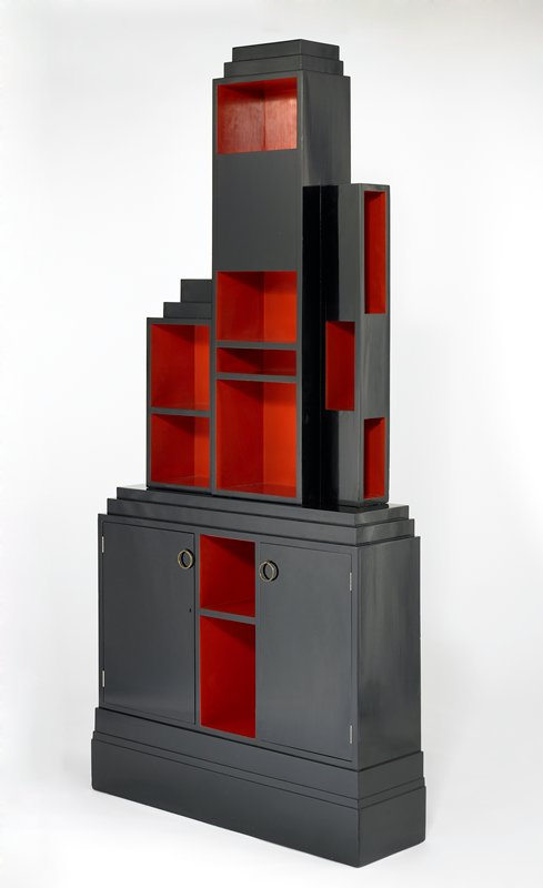 two-piece bookcase with cabinet with two doors and central open shelves between them on bottom; irregular open and closed cubes and rectangles on top section; black with interior of shelves in deep orange