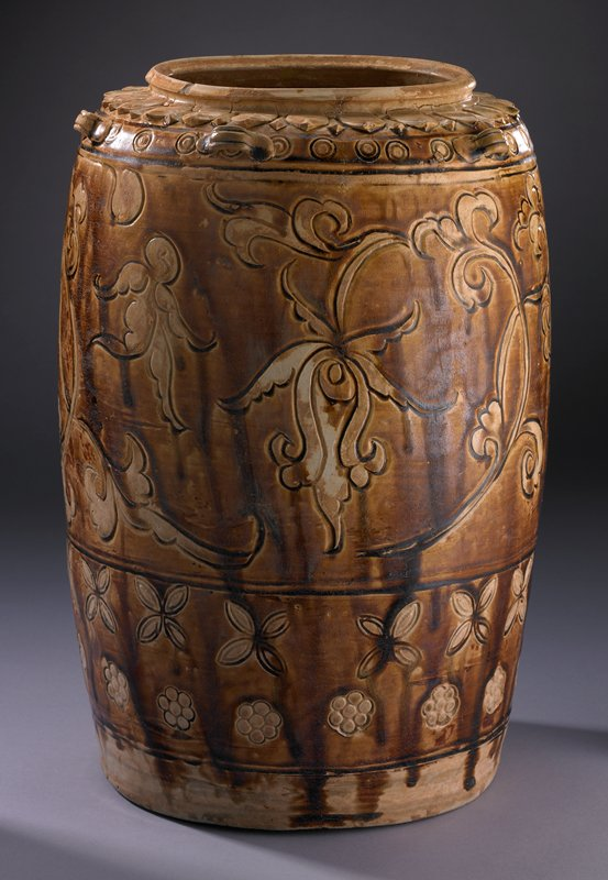 brown dripped glaze over tan vessel; drum-shaped; six small handles and ring of petals at top below lip; incised scrolling chrysanthemum designs and stamped circles, and circle and almond-shaped flower forms