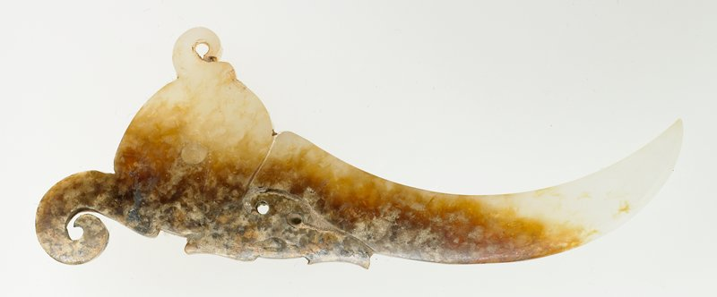 Knot opener with an ornate open work of an animal head; incision and open work. Translucent white jade with brown marks; traces of clay-like substance.