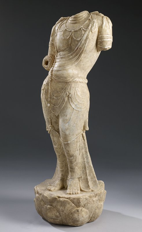 torso and legs of a figure--head, PL arm at bicep and PR arm at elbow lost; clinging drapery; beaded necklace and long beaded strands from PR shoulder, around knees and down center of back; lotus blossom base; cream-colored stone