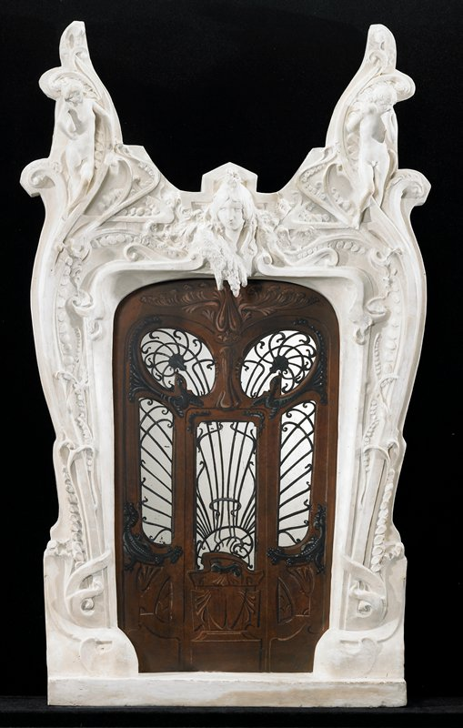 Art Nouveau-style doorway surround with V-shaped top; door itself painted on mirror behind plaster surround; young female nude in ULC, young male nude in URC; woman's head at center above door