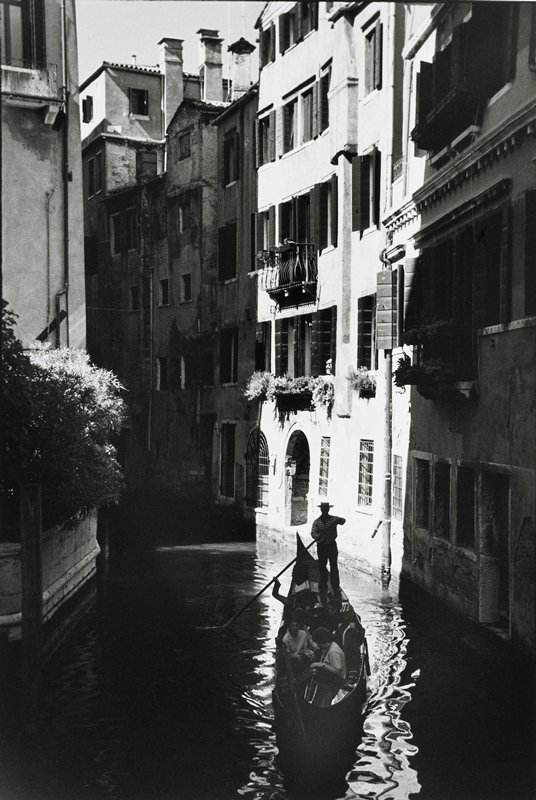 gondolier in a narrow canal with three passengers in gondola