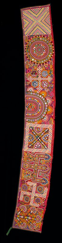 multicolored linear appliqué border on three sides; maroon print backing; red fabric embroidered overall in bright multicolors in organic designs and cross motifs; embellished with mirrors; may be a pair with L2007.114.6