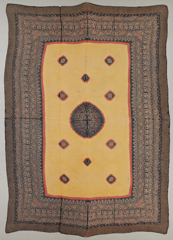 yellow central rectangle bordered with red containing black central medallion with orange and red floral design; ten small circles on either side of medallion; wide black borders with orange and red organic design bands