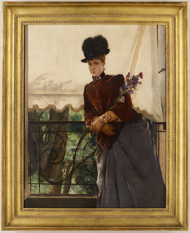 woman wearing a black hat, short maroon cape, long tan gloves and grey skirt, holding purple flowers and leaning on a black iron rail; tan awning behind woman; trees and foliage behind railing