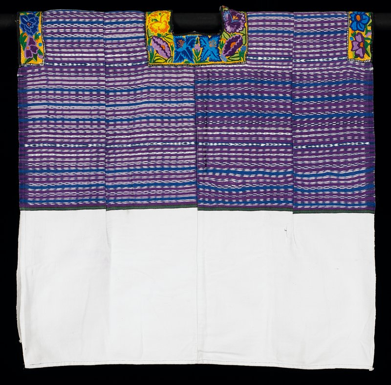 white with top woven with purple, blue, black, green, and blue and white ikat stripes; open sides; shoulders and neckline decorated with embroidery of large multicolored flowers on a yellow ground; square neck opening