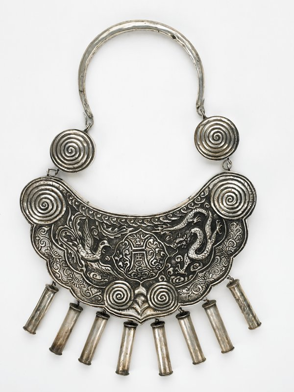 large hollow torque with raised designs; dragon and phoenix on either side of central medallion which has foliate designs surrounding Asian characters; below medallion two spiral designs; two large spirals at top with two more spirals attached with rings to main body; closure attaches with hooks to top rings on uppermost spirals; eight hollow tubes attached to bottom edge; lower edge of body is scalloped foliate designs between spirals on main body