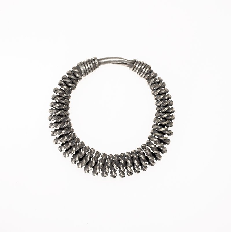bracelet made from twisted and coiled square wire; bracelet is wrapped with thick square wire at the end