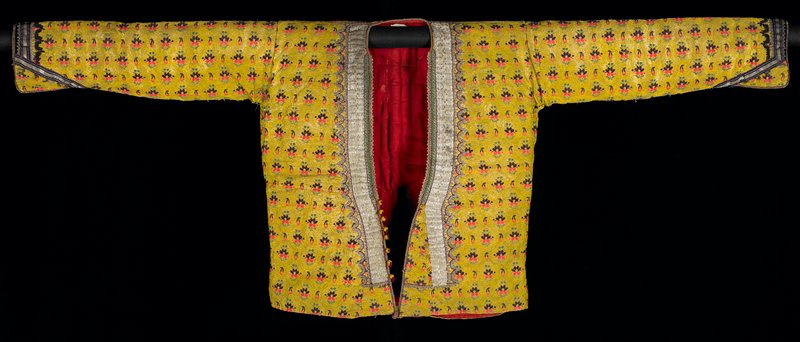 mustard yellow brocade with green, pink and purple flowers; blue and metallic gold trim around cuffs; green, maroon and blue decorative balls at cuffs; small round yellow buttons with maroon tassels; V-neck; neckline trimmed with various gold metallic trims and decoration; red lining