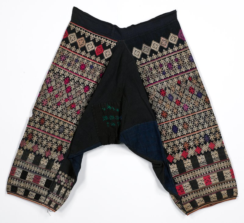 dark indigo, with lighter panels inside each leg; embroidery on outer legs and inner ankles, primarily in white-star/ snowflake, diamond, swastika and geometricized floral motifs; crotch panel has green and blue stitched cross stitch symbols(?)