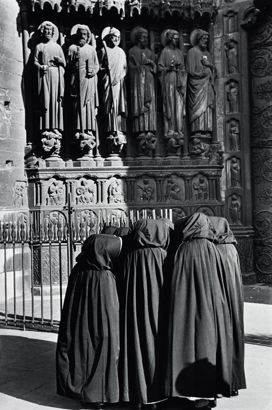 group of figures in dark hooded capes; outer wall of Notre Dame with carved figures in background
