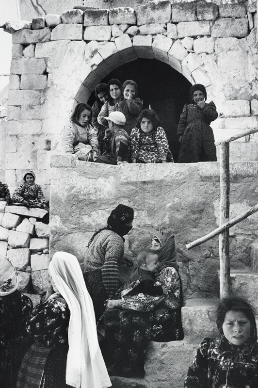 women and children wearing brightly patterned clothing, on and around steps and archway of stone blocks