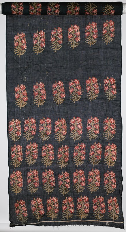 flowers printed on indigo; seven floral motifs across; motifs in tan, red and pink