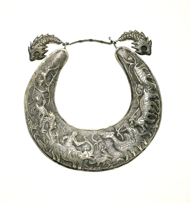 torque; relief motifs include pigs, camel, elephant, dragon, and monkey, also small rabbits, birds, and cats; flowers and foliage along edges; dragon-head hooks; closure is wire wrapped; hook and eye on proper left
