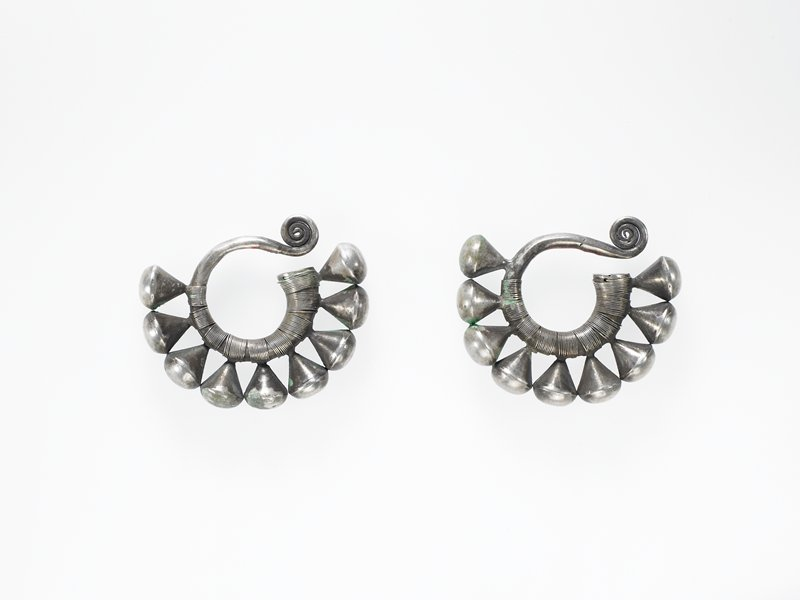 pair of earrings; each earring made from hollow loop of silver with curlicue on one end, a flat piece on other end; loop has nine cones dangling off; small wire is wrapped around loop under the cones