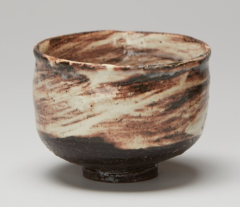 tea bowl; small foot; nearly straight sides, flaring outward very slightly at mouth; cream-colored and brown swirls