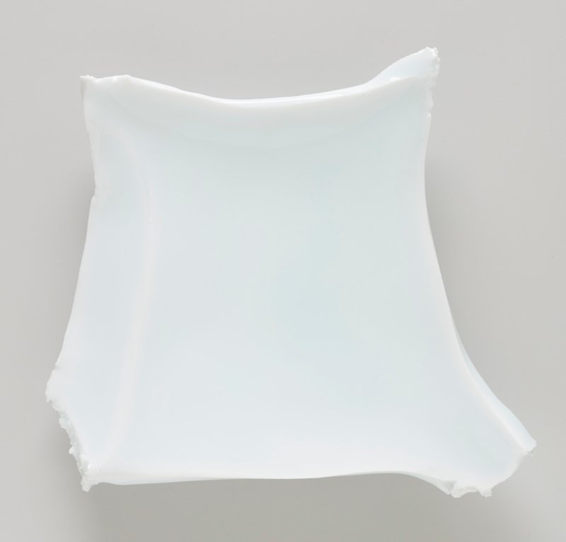 irregular form with three feet; four sides--one side bevelled; torn-off corners; pale blue glaze; white ceramic