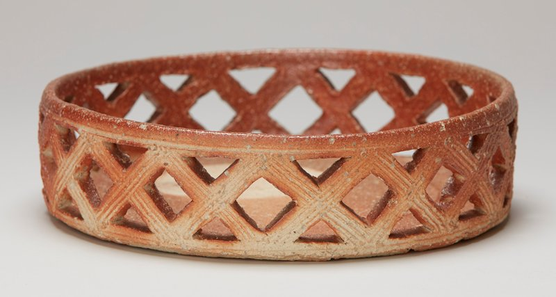 large flat base; vertical bowl sides have openwork band of X's with ribs on exterior; orange and tan with round off-center tan spot at interior bottom