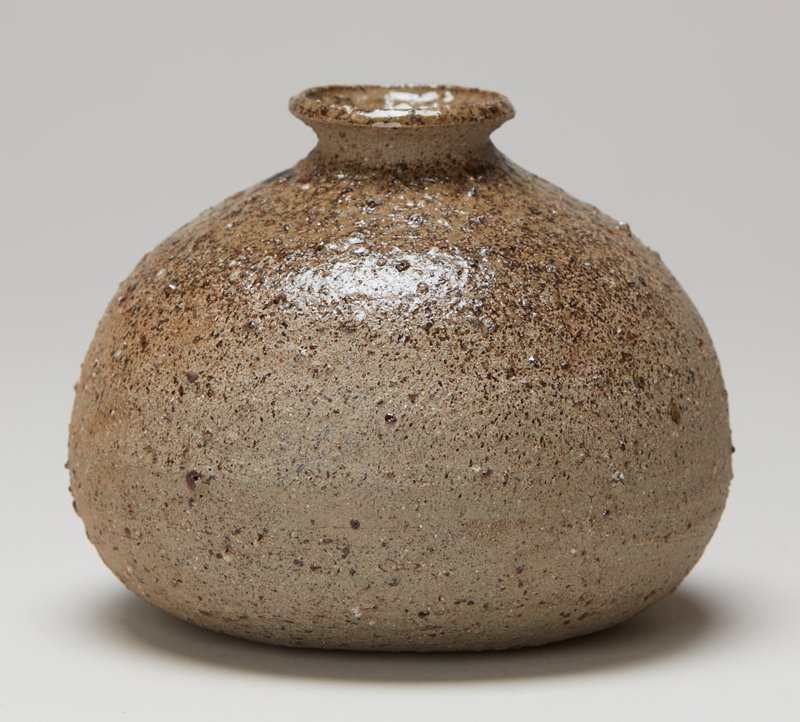 rounded form overall; slightly squat; short neck with outward-flaring mouth; rough texture; shiny grey at top, dull at bottom