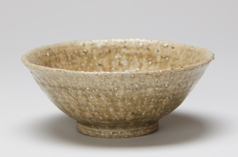 tea bowl; wide ring foot; rounded saucer shape; glaze crackle overall; rough textured surface; green with white spots