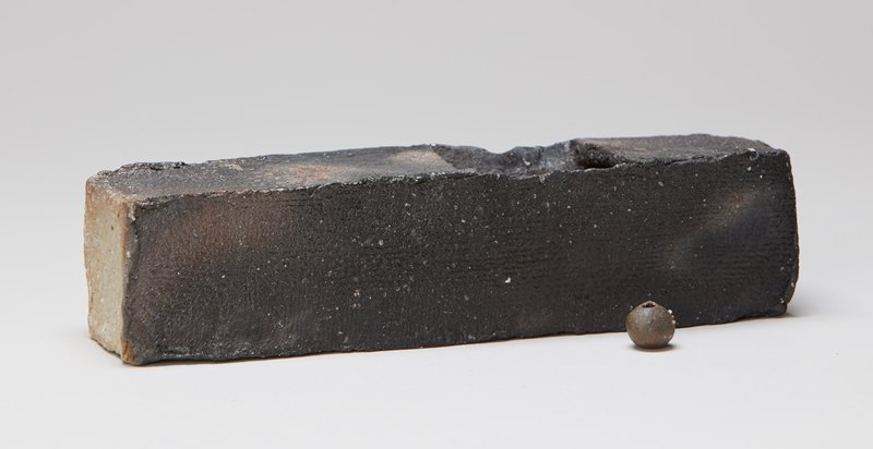rectangular shaped vase with rough form; square off-center top opening; black, light grey and tan; round dark grey bead with hole through it; rough texture