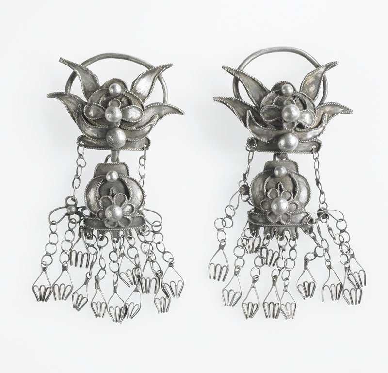 pair of earrings, each upper section: lotus flower-like design; lower section: flower motif with semi-circular foliate motif on either side; two pendants from upper section have three smaller pendants attached to four-lobed chain; five small pendants from center motif