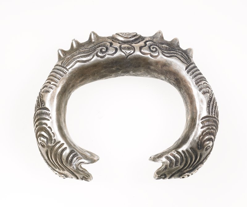 dragon bracelet; hollow; center motif oval with fish-like creatures in center; three raised spikes on either side of oval; cloud-like motifs on sides; layered scale-like designs behind heads