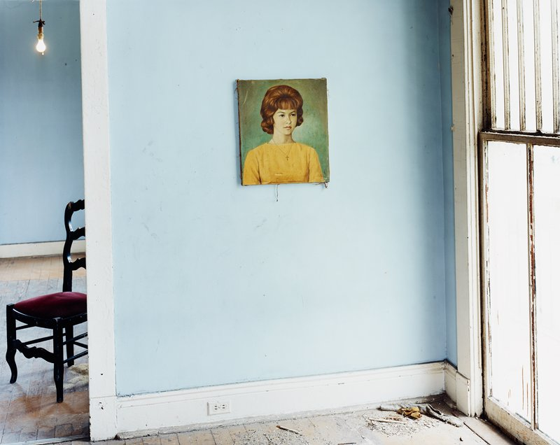blue wall with white trim; painted portrait of a woman wearing a yellow blouse; debris on floor; black chair with maroon seat through doorway at left; bare bulb, ULC