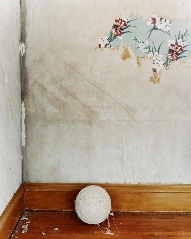 big ball of twine on wood floor; grey worn walls with flowered wallpaper remnant