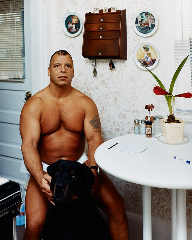 muscular man with tatoo of PL arm, wearing underpants and a watch, seated in a kitchen; large black dog in front of man
