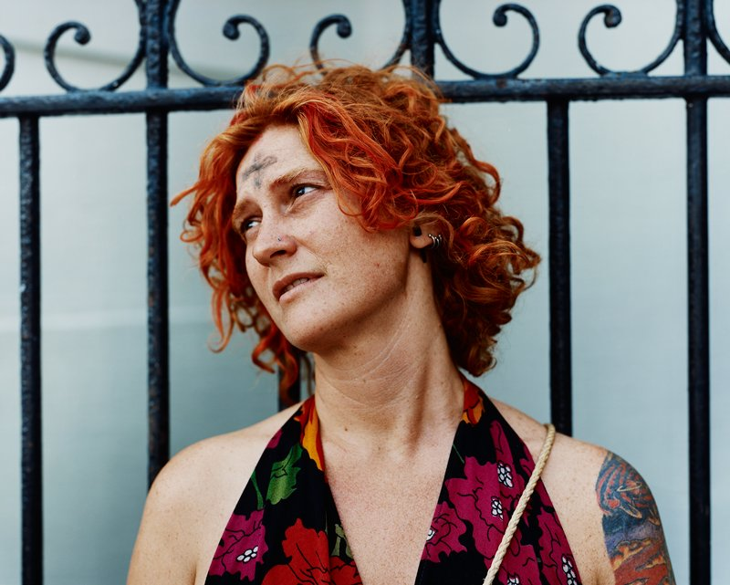 portrait of woman with red curly hair wearing blue nose stud, large black ear plug and silver earrings, tattoo on PL shoulder, standing against black iron fence