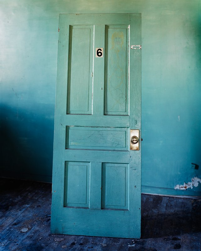 "blue-green wall; blue-green dor leaning against wall; ""6"" label on door; drawing of blonde figure on door; black floor"