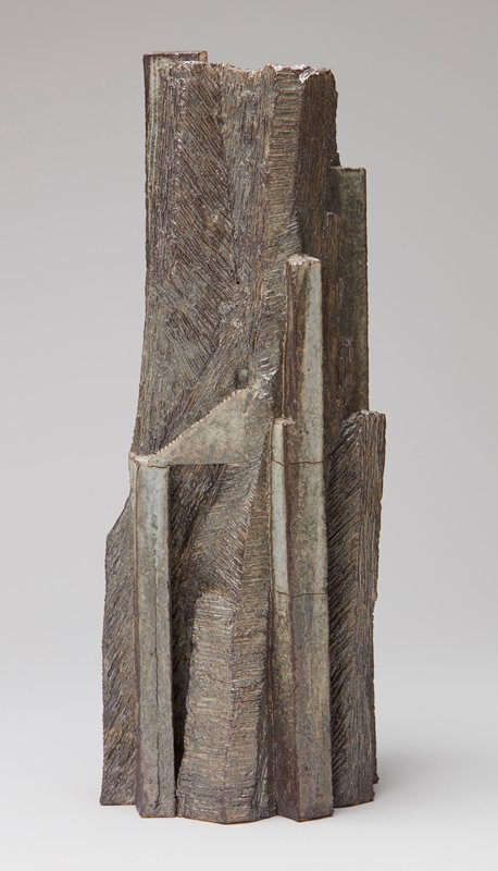 flat bottom; tall sculptural form with predominately vertical angular facets, some with etched faces; grey with milky white exterior; milky white interior