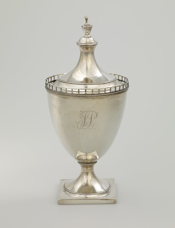 """urn shape with square base; openwork geometric """"rail"""" at top rim with bead row below; cover with finial; engraved looping design may be stylized monogram (SP?)"""