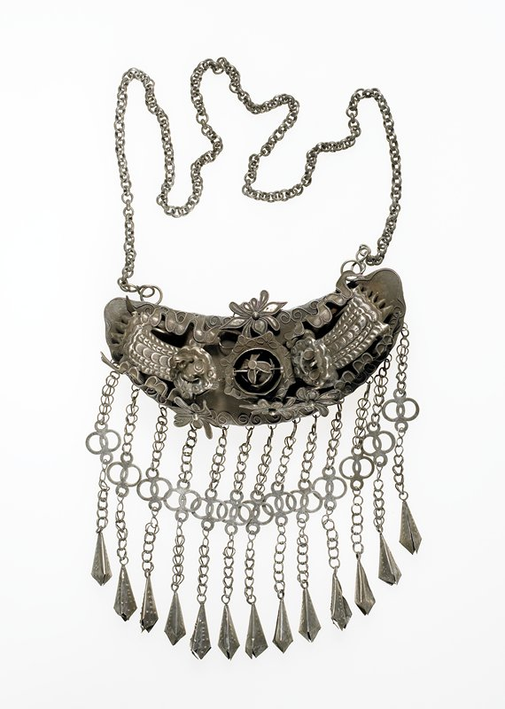 pendant necklace; semi-circular with applied designs; two round-head, open-mouth creatures with dragon-like bodies; moveable heads; ball inside center floral motif moves; four butterfly-like motifs and a wave-like design attached to main section; 13 cone-shaped pendants attached at bottom; a four-lobed, floral-like design between top section and cones