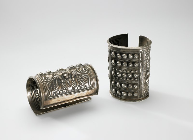 one of a pair of cuff bracelets; bracelet has lip around all edges; bracelet has three panels; the panels on each end have two birds with a sphere between them; the panel in the center has five lines of five spheres in relief
