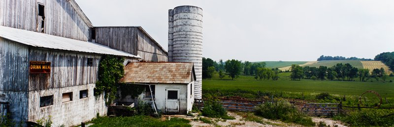 "barn with several additions and open silo at left; dry grey wood; rusted sign at left: ""Enjoy Good Health...DRINK MILK""; farm fields and rows of trees at right"