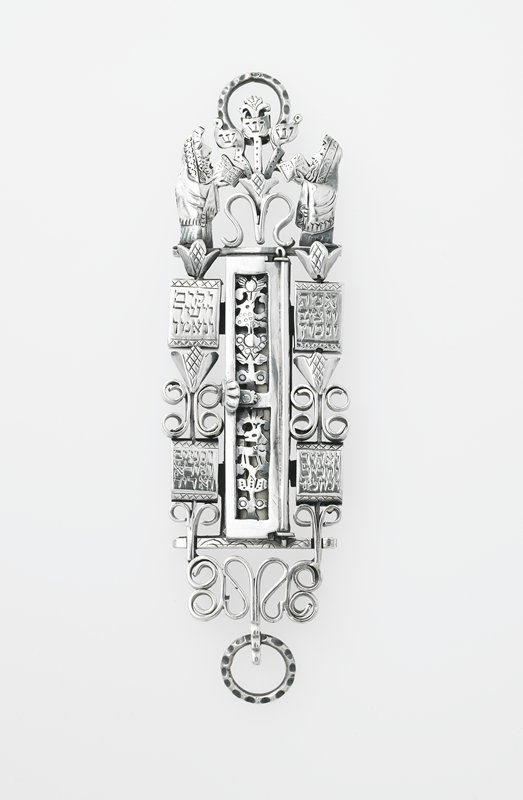 two figures at top, wearing shawls and holding books; three elements between figures; openwork scrolls and tulips at edges and bottom; openwork door with flowers, bird and deer; four panels at sides with Hebrew engraved text; paper scroll inside