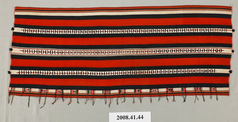 red, black and white stripes; four strips stitched together with red thread with black decorative chevrons; one long side has bow tie-shaped woven elements in pink, red, black, orange, green and white with twisted tassels