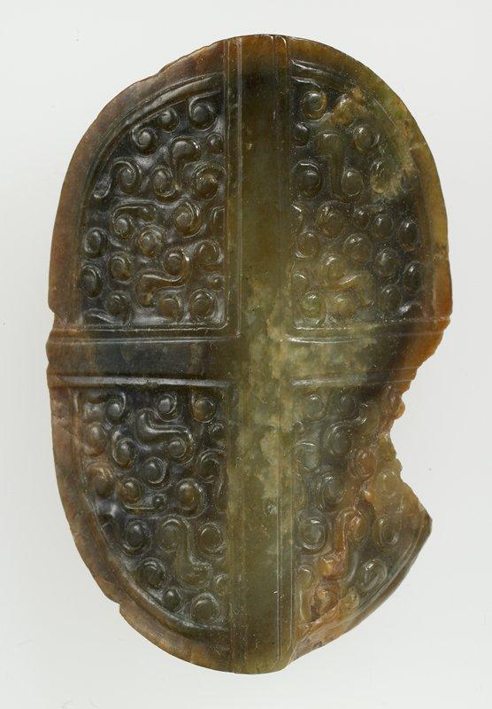 Mottled olive-green jade. Oblong plaque resembles miniature shield.